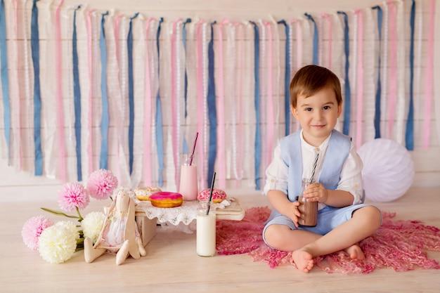 Un niño come donas y bebe leche de una pajita