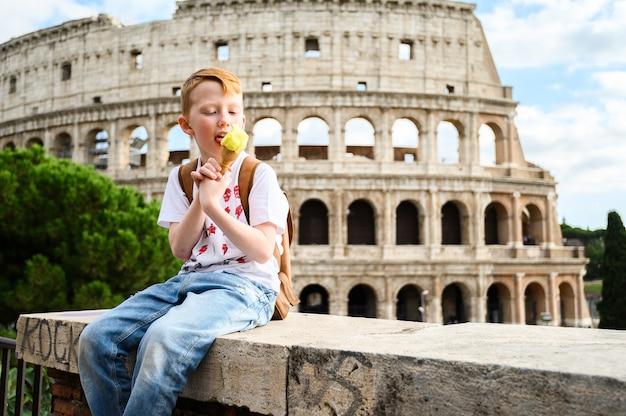 Un niño come helado en el coliseo. italia, roma