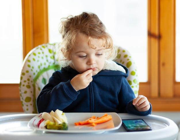 El niño come mientras mira películas en el teléfono móvil.