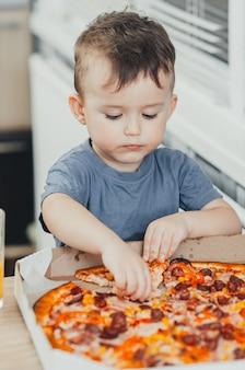 El niño se come una pizza enorme y dañina él mismo en la cocina y bebe jugo, muy graso y dañino.