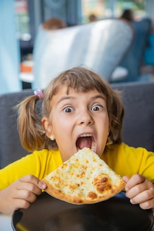 El niño come pizza de queso.