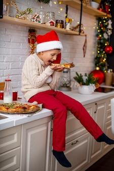El niño come un trozo de pizza caliente