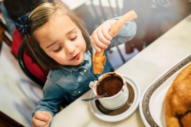 Niño comiendo churros y chocolate.