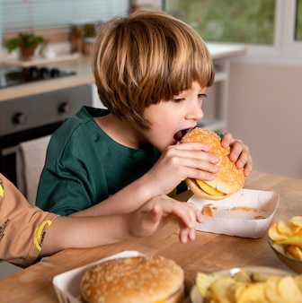 Niño comiendo hamburguesas en casa