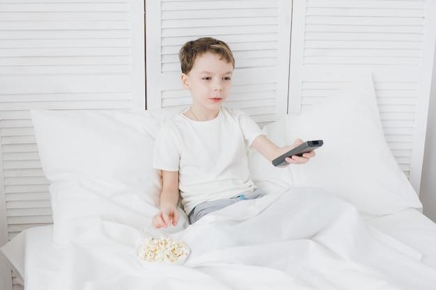 Niño comiendo palomitas de maíz sentado en la cama y viendo la televisión