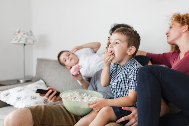 Niño comiendo palomitas mientras ve televisión con sus padres. Foto Premium