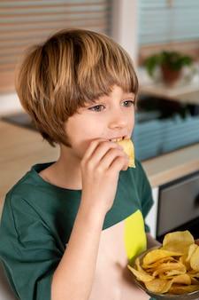 Niño comiendo patatas fritas en casa