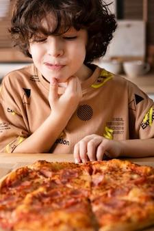Niño comiendo pizza en casa