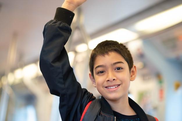 Niño comprando boleto eléctrico y caminando en la estación de tren público con la familia