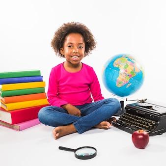 Niño con libros globo y máquina de escribir en estudio