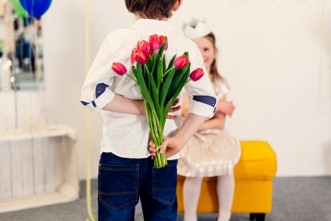 Niño con tulipanes rosas detrás