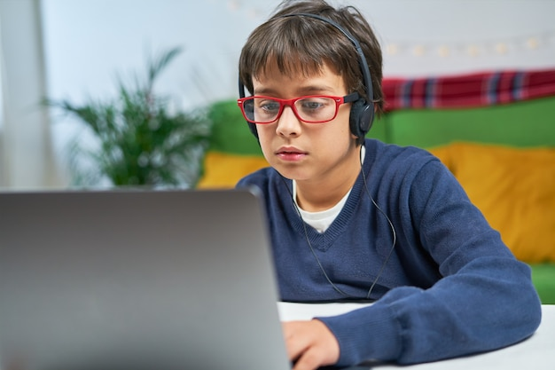 Un niño concentrado usando laptop, usando audífonos, sentado solo en casa