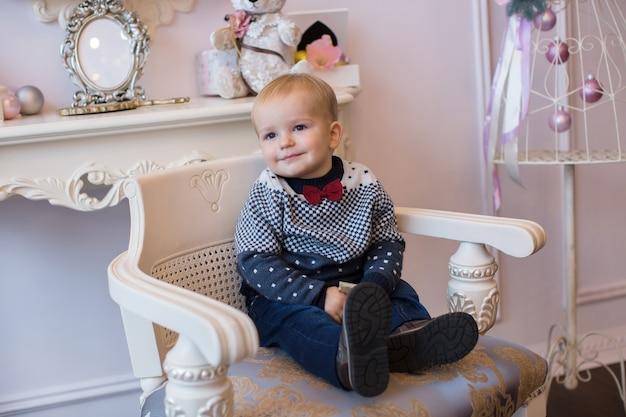 El niño de la corbata roja sentado en una silla en el interior de año nuevo.