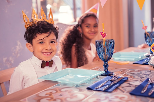 Niño con corona de papel en la fiesta de cumpleaños