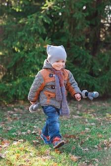 El niño corre al parque otoño.