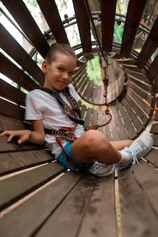 Niño corre una carrera de obstáculos en un parque de cuerdas