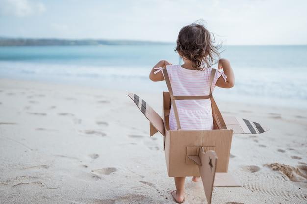 Niño corre en la playa juega con avión de juguete hecho de cartón