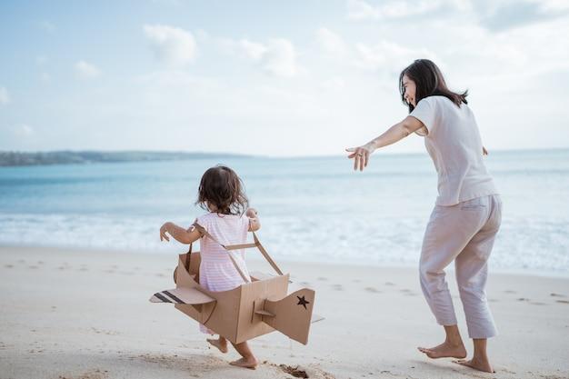 Niño corriendo en la playa juega con avión de juguete de cartón con mamá