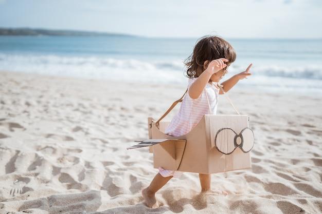 Niño corriendo en la playa jugar con avión de juguete de cartón