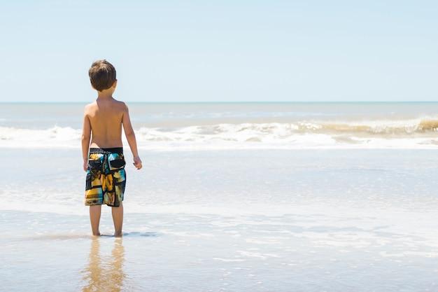 Niño en la costa en el agua
