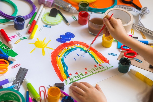 Niño creando un dibujo con un arco iris