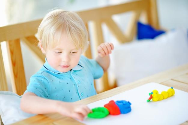 Niño creativo jugando con plastilina de colores en el jardín de infantes.