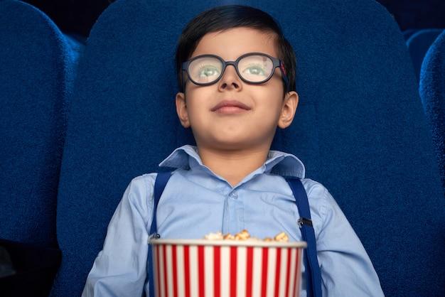 Niño con cubo de palomitas de maíz viendo dibujos animados en el cine.