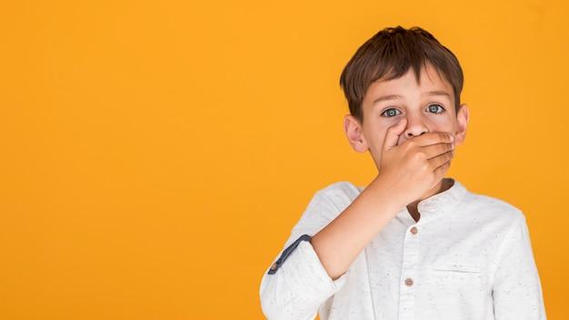Niño cubriendo su boca con espacio de copia