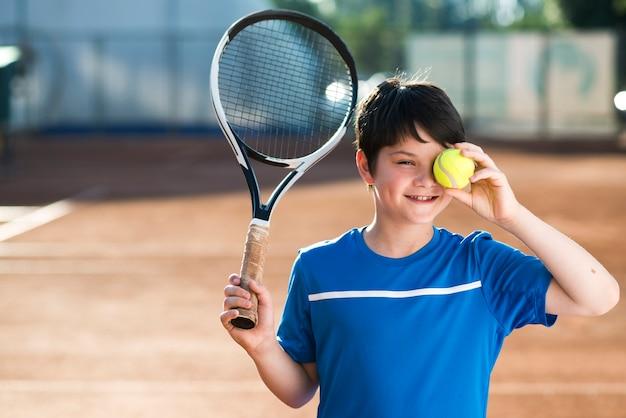 Niño cubriendo su ojo con una pelota de tenis