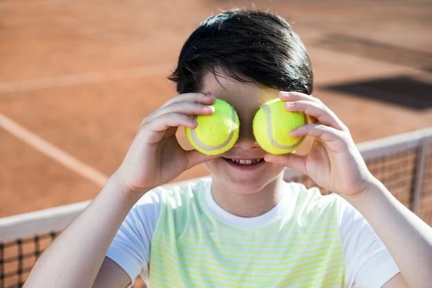 Niño cubriéndose los ojos con pelotas de tenis.