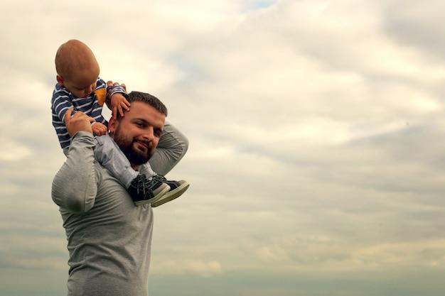 Un niño en el cuello de su padre. camina cerca del agua. bebé y papá contra el cielo.