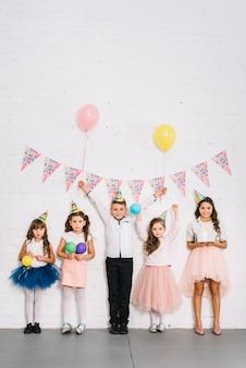 Niño de cumpleaños de pie con las niñas contra la pared blanca decorada con banderines
