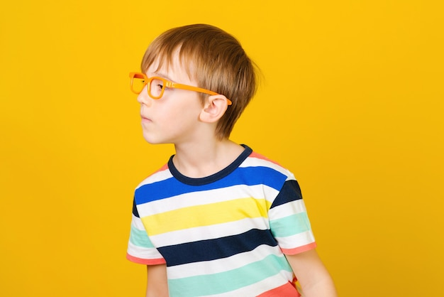 Niño curioso mirando a un lado y escucha algo. chico inteligente en vasos sobre fondo amarillo.