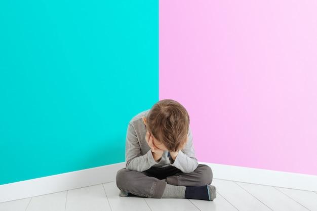 Niño cuya depresión está sentada en el piso