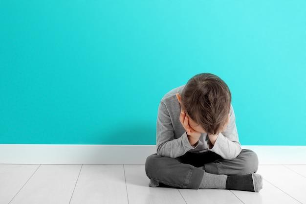 Un niño cuya depresión está sentada en el suelo.