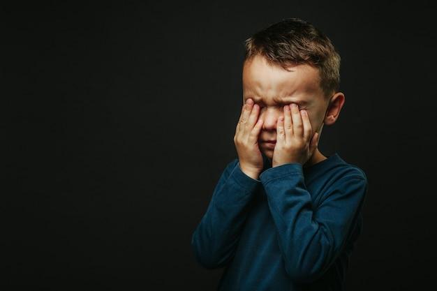 Un niño cuya depresión está en un walld negro con las manos cerradas.