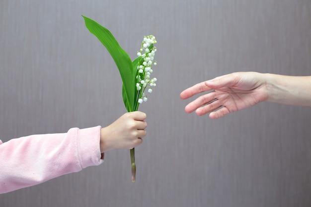 Niño le da flores a mamá