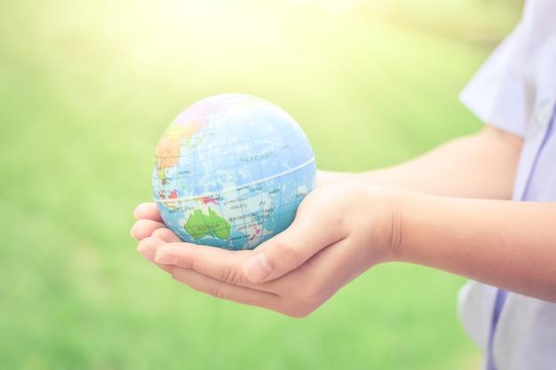 El niño da sostener el concepto de la tierra para cuidar el planeta o ahorrar concepto de la tierra.