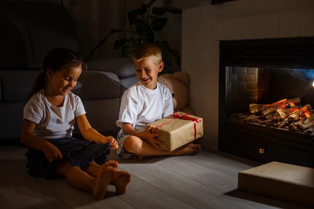 Niño dando una caja de regalo con cinta roja para niña, hermanos sentados cerca de una chimenea