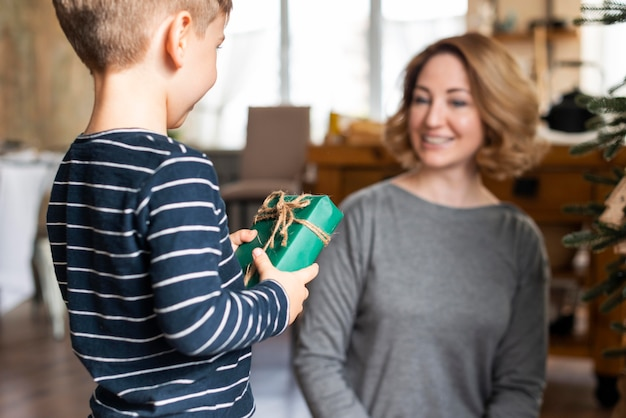 Niño dando regalo de navidad a la madre