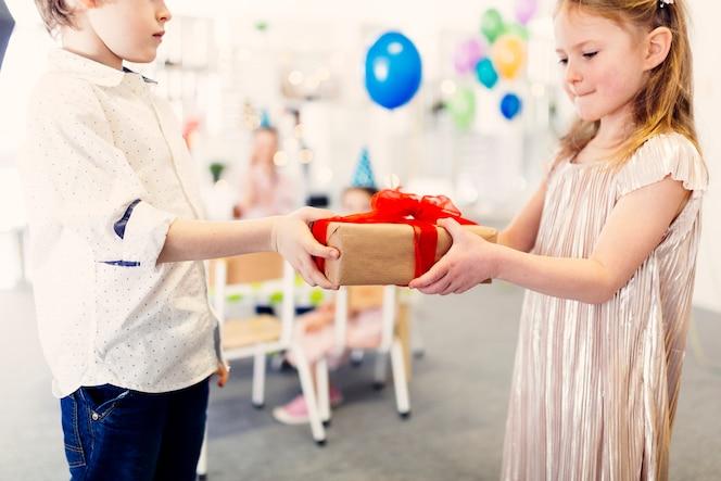 Niño dando un regalo a una amiga