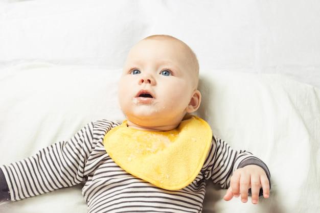 Niño con delantal amarillo para niños con residuos de comida se sienta en una cama blanca después de comer.