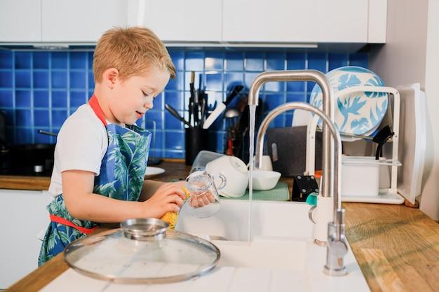 Un niño en un delantal lava platos en la cocina de su casa.