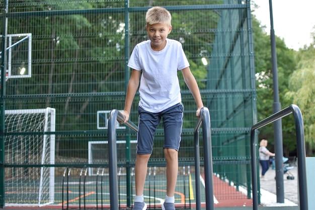 Niño en deportes callejeros hace ejercicios gimnásticos. campo de deportes al aire libre de la ciudad.
