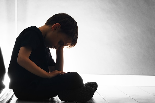 Niño con depresión está sentado en el suelo