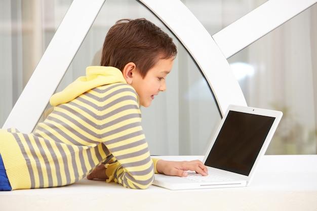 Niño descansando con el ordenador portátil