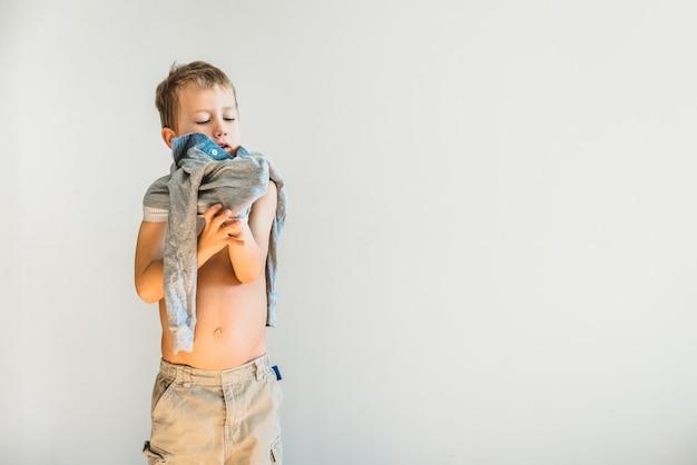 Niño desnudándose antes de irse a dormir, solo, aprendiendo a ser independiente.