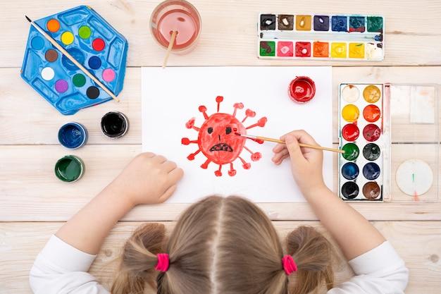 Un niño dibuja un coronovirus en una hoja de papel. el dibujo fue hecho por un niño usando pinturas de colores.