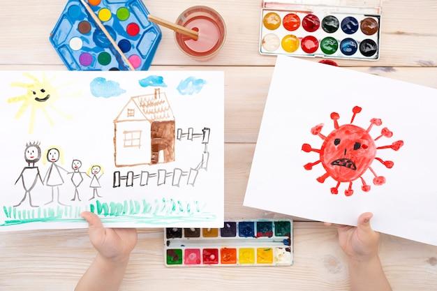 Un niño dibuja un coronovirus y su familia en una hoja de papel.