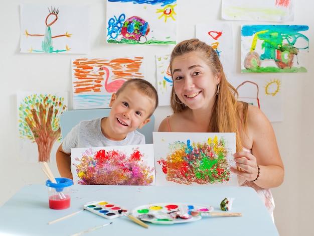 Niño dibuja con la maestra